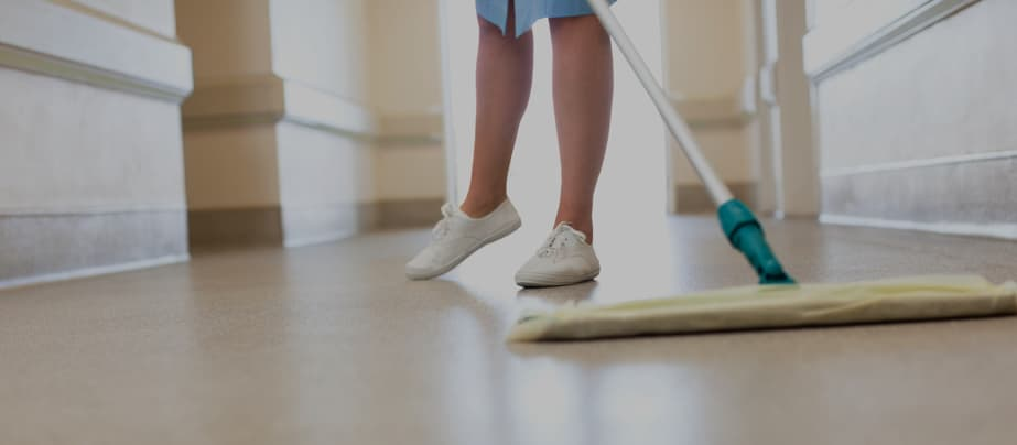 A person cleaning the floor at a long-term care facility.